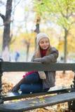 哀伤的女孩坐一条长凳在公园 免版税库存图片