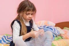 哀伤的女孩坐床和吃在包装的影片的泡影 库存图片