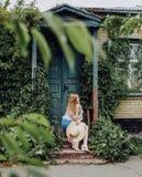 哀伤的女孩坐的等待的步老房子 库存照片