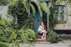 哀伤的女孩坐的等待的步老房子 免版税库存图片