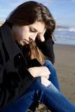 哀伤的女孩想法的坐海滩在冬天 免版税库存图片