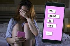 哀伤的女孩感觉沮丧的哭泣在床遭受的痛苦中和与手机网上文本的伤心综合在关系 免版税库存图片