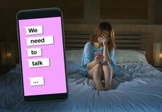 哀伤的女孩感觉沮丧的哭泣在床遭受的痛苦中和与手机网上文本的伤心综合在关系 库存图片