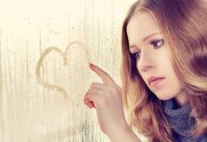 哀伤的女孩画在视窗的一个重点在雨中 免版税库存图片