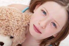 哀伤的女孩藏品玩具熊和哭泣 免版税库存图片