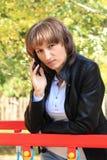 哀伤的女孩谈话由一个手机 库存图片
