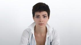 哀伤的女实业家剧烈的画象白色衬衣的有看观察者的浮动的头发的 免版税图库摄影