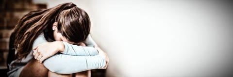 哀伤的女小学生单独坐楼梯 图库摄影