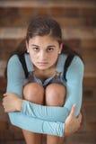 哀伤的女小学生画象单独坐楼梯 免版税库存照片