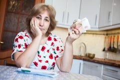 哀伤的女性领抚恤金者显示现金金钱,当坐在与票据的厨房用桌上付款的时 图库摄影