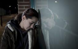 哀伤的妇女单独倾斜在哭泣在痛苦中的夜遭受的消沉的街道窗口 库存图片
