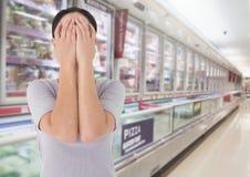 哀伤的妇女哀情移交面孔反对超级市场背景 免版税库存照片