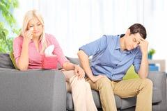 哀伤的妇女在家争论与她的丈夫 免版税图库摄影