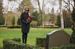 哀伤的妇女在拿着玫瑰的公墓追悼 免版税库存照片