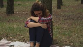 哀伤的妇女在森林里坐在树附近 股票视频