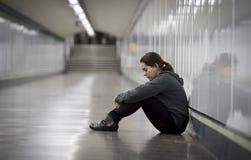 年轻哀伤的妇女在痛苦中单独和沮丧在都市地铁tunn 库存照片