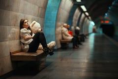 哀伤的妇女坐在地铁的一条长凳 免版税库存照片