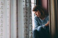 年轻哀伤的妇女坐窗口 免版税图库摄影