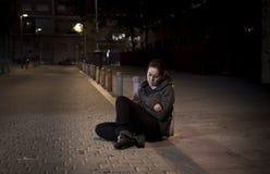 年轻哀伤的妇女坐街道地面在夜单独绝望遭受的消沉留给被放弃 免版税图库摄影