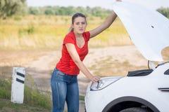 哀伤的妇女画象打开了残破的汽车敞篷在领域的 库存照片