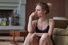 年轻哀伤的妇女画象在家坐地板 免版税库存图片