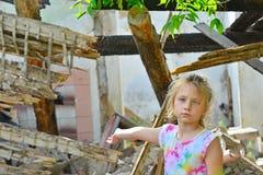 哀伤的孤儿女孩被留下无家可归者和点对被破坏的大厦的废墟由于一次军事冲突的火 免版税库存图片