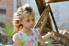 哀伤的孤儿女孩被留下无家可归者和点对被破坏的大厦的废墟由于一次军事冲突的火 免版税库存照片