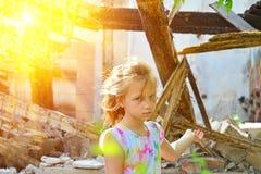 哀伤的孤儿女孩被留下无家可归者和点对被破坏的大厦的废墟由于一次军事冲突的火 库存图片