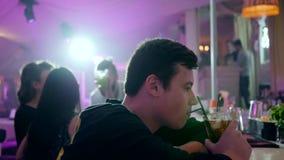 哀伤的孤独的人喝在酒吧柜台后的酒精鸡尾酒在光背景的俱乐部  股票录像