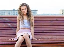 哀伤的孤独的女孩坐一条长凳每温暖的夏日在城市 库存图片