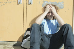 哀伤的孤独的男孩在学校操场 库存图片