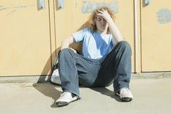 哀伤的孤独的男孩在学校操场 免版税库存图片