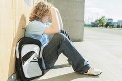 哀伤的孤独的男孩在学校操场 免版税图库摄影