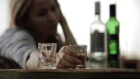 哀伤的孤独的从玻璃的妇女饮用的酒精在酒吧 女性酒精中毒、情感不稳定和社会紧张 股票录像
