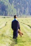 哀伤的孩子在草甸拿着一个棕色玩具熊 回到视图 复制空间 悲伤,恐惧,失望,寂寞 图库摄影