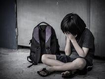 哀伤的孩子坐与书包等待的父母的地板 免版税库存照片