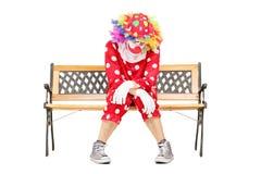 哀伤的小丑坐一个长木凳 库存照片