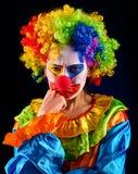 哀伤的小丑黑色背景 有牙痛的病的妇女在表现以后 免版税库存照片