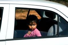 哀伤的小女孩单独坐在汽车和 免版税库存图片