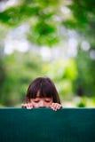 哀伤的小女孩坐长凳 免版税库存照片