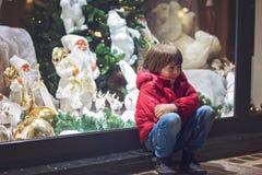哀伤的小孩,与玩具的观看的圣诞节装饰在s 库存照片