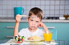 哀伤的小男孩坐在餐桌和看意粉上 免版税库存照片