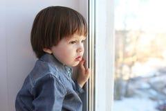 哀伤的小男孩看在窗口外面 免版税库存照片