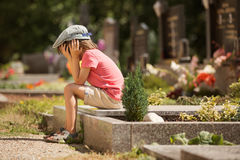 哀伤的小男孩,坐一个坟墓在公墓,感到哀伤 免版税库存图片