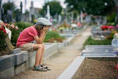 哀伤的小男孩,坐一个坟墓在公墓,感到哀伤 库存照片
