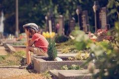 哀伤的小男孩,坐一个坟墓在公墓,感到哀伤 免版税库存照片