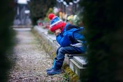 哀伤的小男孩,坐一个坟墓在公墓 免版税库存图片