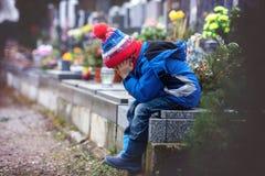 哀伤的小男孩,坐一个坟墓在公墓 库存照片
