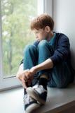 哀伤的少年坐窗口 库存图片