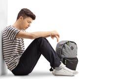 哀伤的少年学生坐地板 库存图片